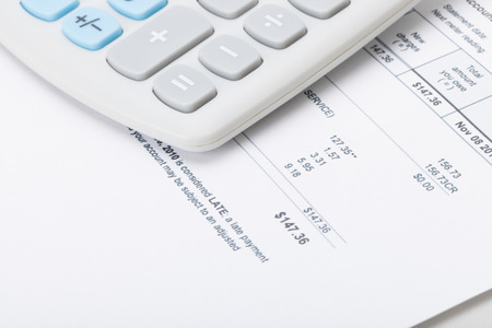 utility payments: Calculator over utility bill
