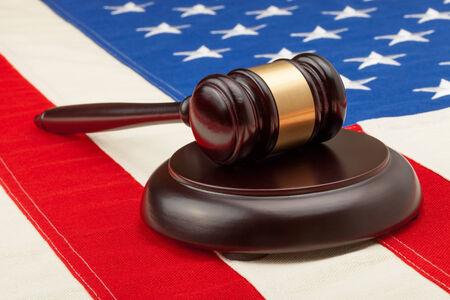 Wooden judge gavel and soundboard laying over USA flag - studio shoot photo