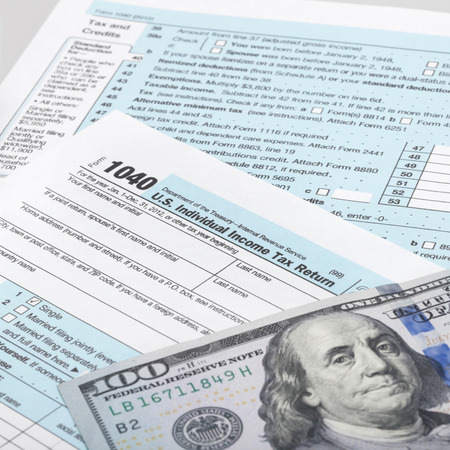 taxpayer: USA Tax Form 1040 with calculator and 100 US dollar bills - 1 to 1 ratio