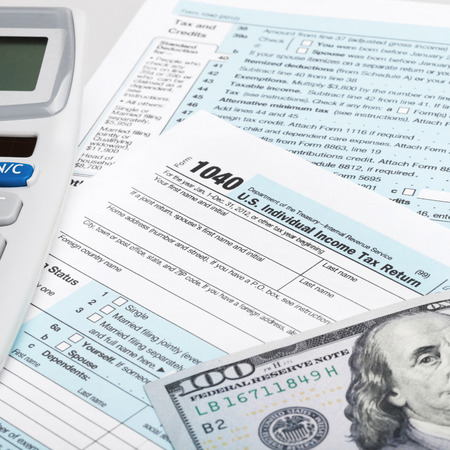taxable income: USA Tax Form 1040 with calculator and 100 US dollar bills