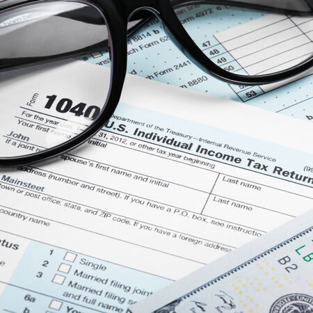 taxable income: USA Tax Form 1040 with glasses and 100 US dollar bills