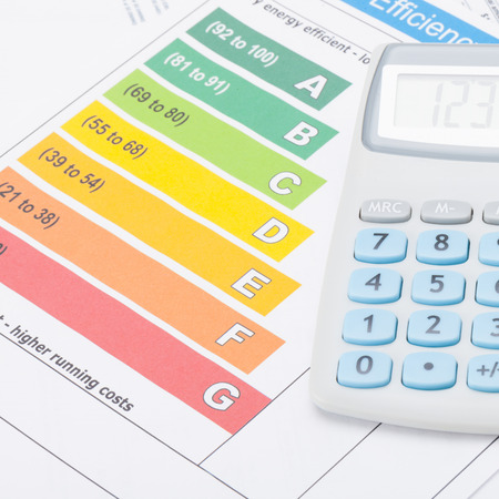 utility payments: Calculator over energy efficiency chart  Stock Photo