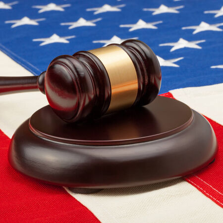 international criminal court: Wooden judge gavel and soundboard laying over USA flag  Stock Photo