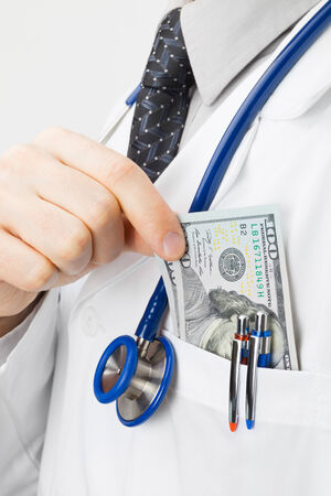 doctor putting money: Doctor putting money into his pocket - studio shoot Stock Photo