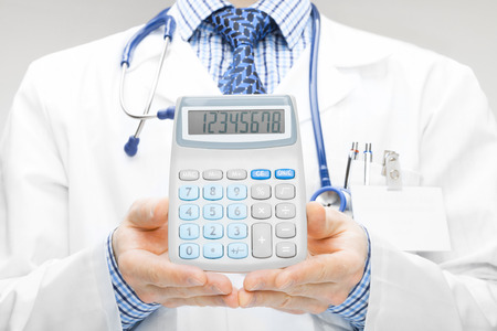 Medical doctor with calculator in his hand - studio shoot photo