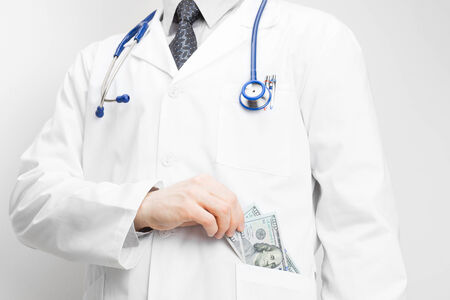 putting money in pocket: Doctor putting money into his pocket with his left hand