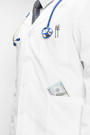 Doctor with money into his pocket and hands behind his back photo