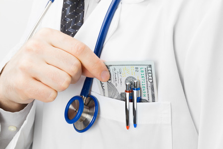 putting money in pocket: Doctor putting money into his pocket - closeup studio shot Stock Photo