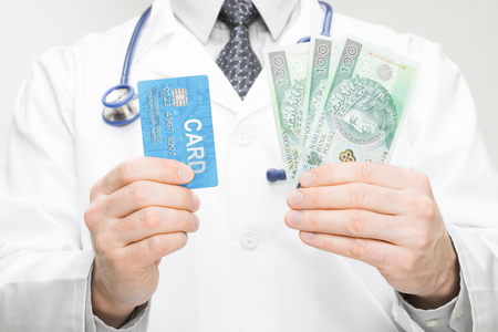 Doctor holding money and credit card in his hand - closeup studio shot photo