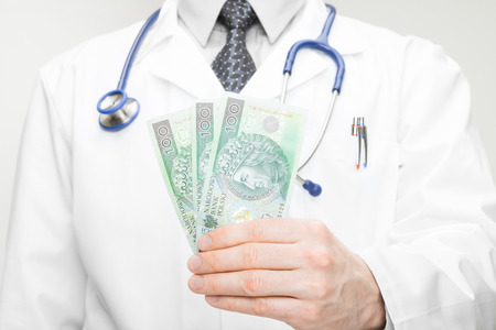 Doctor holding money in his hand - closeup studio shot photo