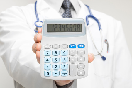 doctor holding money: Medical doctor with calculator in his hand - closeup shot Stock Photo