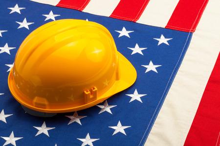 Construction helmet laying over USA flag - closeup shoot