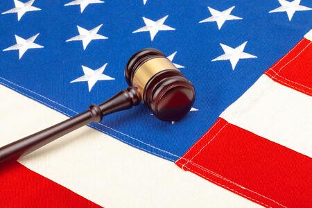 Wooden judge gavel over US flag photo