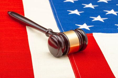 Wooden judge gavel over US flag - closeup studio shot photo