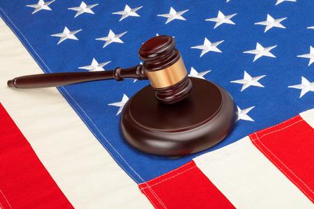 Wooden judge gavel and soundboard laying over US flag - closeup shot photo