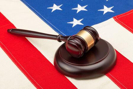 Wooden judge gavel and soundboard laying over USA flag - closeup shot photo