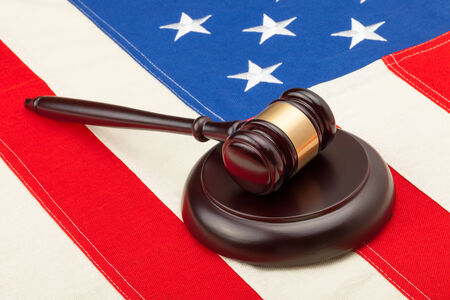 international criminal court: Wooden judge gavel and soundboard laying over USA flag - closeup shot