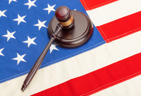 international criminal court: Wooden judge gavel and soundboard laying over US flag Stock Photo