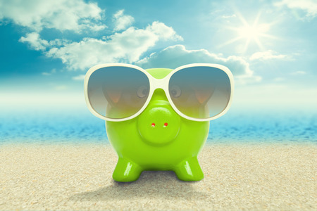 Piggy bank in sunglasses on the beach - vacation concept