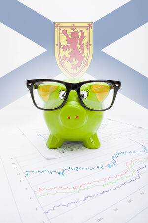 Piggy bank with Canadian province flag on background - Nova Scotia photo