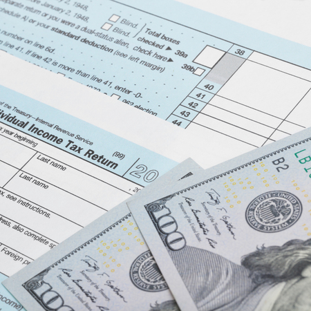 taxable: USA Tax Form 1040 with 100 US dollar bills - 1 to 1 ratio