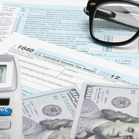 taxable: USA Tax Form 1040 with glasses, calculator and 100 US dollar bills - 1 to 1 ratio