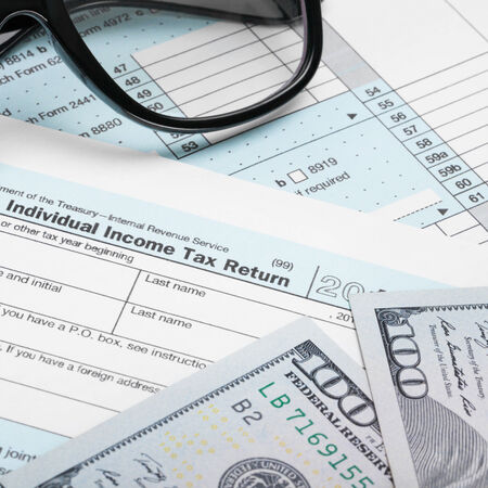 taxable income: USA Tax Form 1040 with glasses and 100 US dollar bills - 1 to 1 ratio Stock Photo