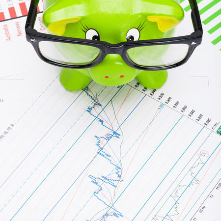 Green piggy bank over stock market chart - view from top - 1 to 1 ratio photo