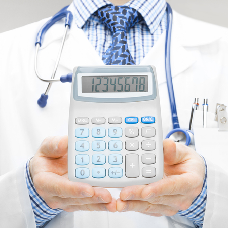 Medical doctor with calculator in his hand - studio shoot - 1 to 1 ratio photo
