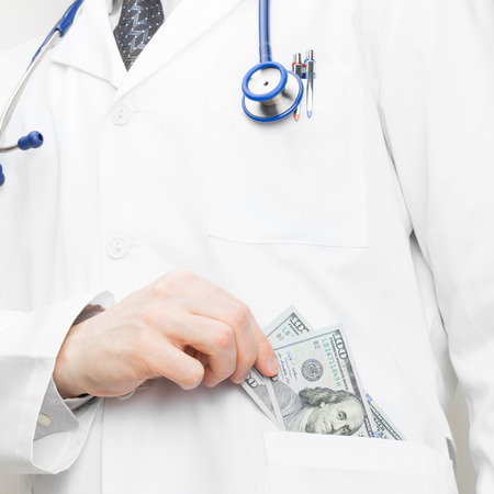 doctor putting money: Doctor putting money into his pocket - 1 to 1 ratio