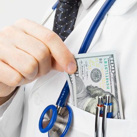 putting money in pocket: Doctor putting money into his pocket - studio shoot - 1 to 1 ratio