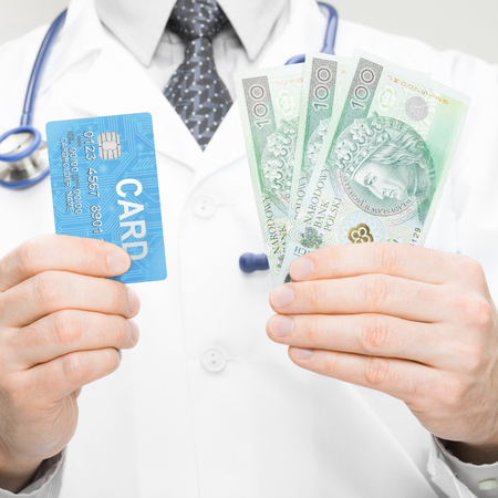 doctor holding money: Doctor holding money and credit card in his hand - closeup studio shot - 1 to 1 ratio Stock Photo