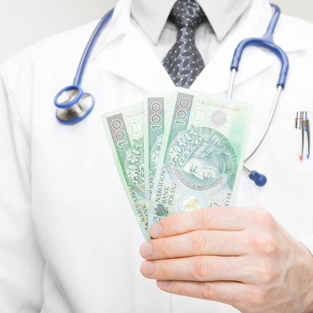 Doctor holding money in his hand - closeup studio shot - 1 to 1 ratio photo