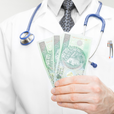 corruptible: Doctor holding money in his hand - closeup studio shot - 1 to 1 ratio Stock Photo