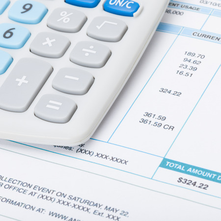 utility payments: Receipt next to calculator - studio shot - 1 to 1 ratio Stock Photo