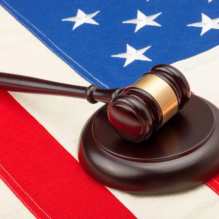Wooden judge gavel and soundboard laying over USA flag - closeup shot - 1 to 1 ratio photo
