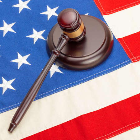 Wooden judge gavel and soundboard laying over US flag - 1 to 1 ratio photo
