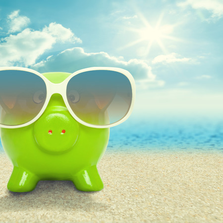 Piggy bank in sunglasses on the beach - vacation concept - 1 to 1 ratio photo