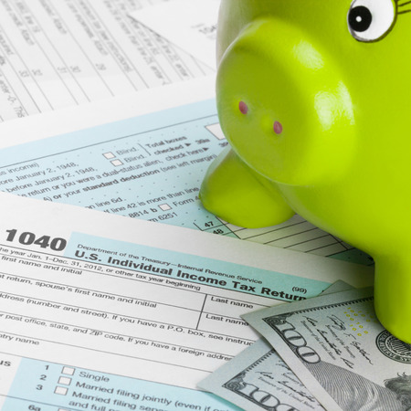taxable: US Tax Form 1040 with piggy bank and 100 dollars