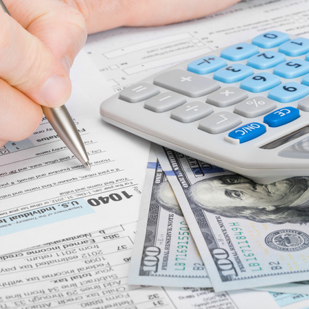 Male filling out 1040 US Tax Form with calculator and money on table - 1 to 1 ratio