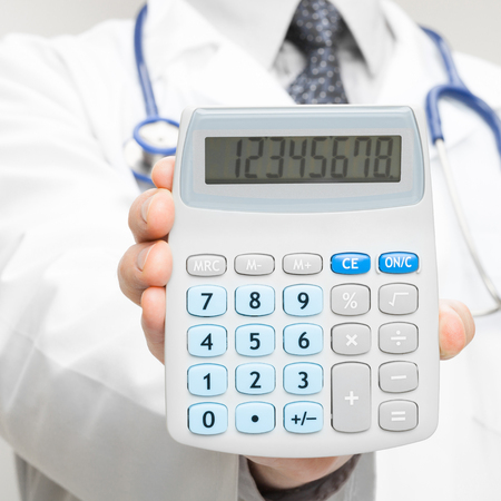 Medical doctor holding in his hand calculator photo