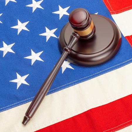 Wooden judge gavel and soundboard laying over big US flag  photo