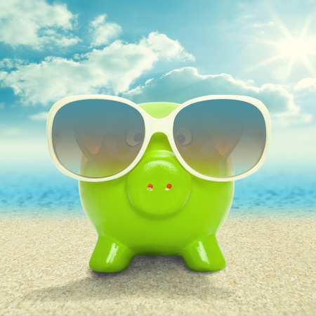 Piggy bank in white sunglasses on the beach - vacation concept photo