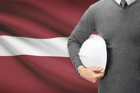 architector: Architect with flag on background  - Latvia Stock Photo