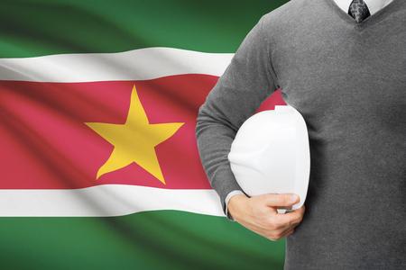 architector: Architect with flag on background  - Suriname Stock Photo