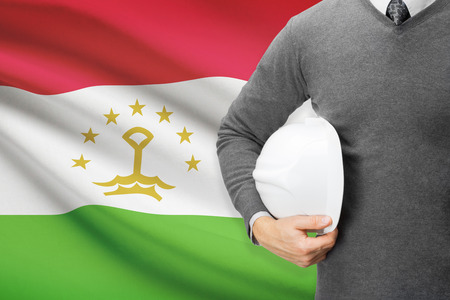 architector: Architect with flag on background  - Tajikistan Stock Photo