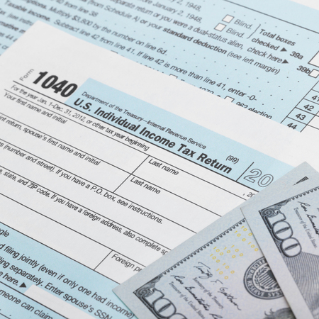 taxable: US Tax Form 1040 with 100 dollars bills - 1 to 1 ratio Stock Photo