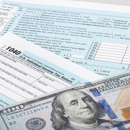 taxable: USA Tax Form 1040 with calculator and 100 dollars bills  Stock Photo