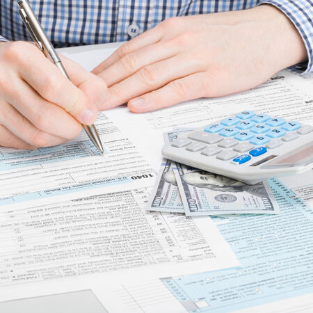 taxable income: Man filling out 1040 US Tax Form - studio shot - 1 to 1 ratio