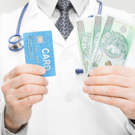 Doctor holding money and credit card - 1 to 1 ratio photo